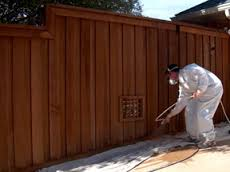 Shambaugh painting spraying finish on this bettendorf fence